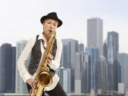 Saxophonist. Woman playing on saxophone against the background of skyscraper photo