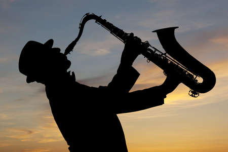 jazz music: Saxophonist. Man playing on saxophone against the background of sunset