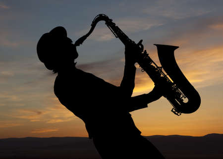 musician silhouette: Saxophonist. Woman playing on saxophone against the background of sunset