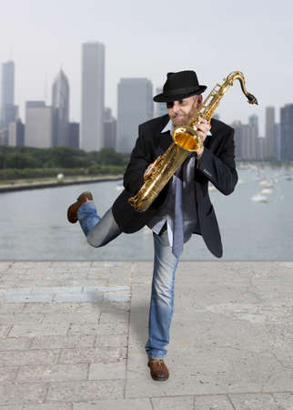 young musician: Saxophonist. Middle aged man playing on saxophone against the background of skyscraper