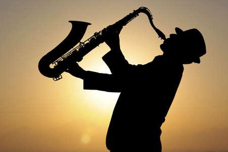 saxofon: Saxofonista. Hombre que toca el saxofón en el contexto de la puesta del sol