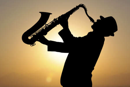the blues: Saxophonist. Man playing on saxophone against the background of sunset