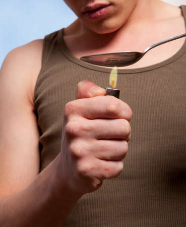 risky behavior: Man with a hardline drug addiction heating drugs in a spoon over a flame  Stock Photo
