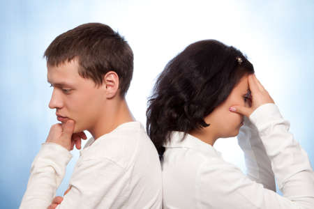 lovers quarrel: Young couple quarreling against a blue background  Stock Photo