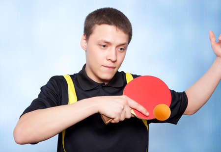 Young man playing table tennis against a blue background  photo