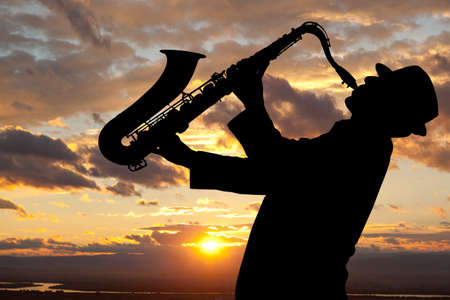 tenor: Saxophonist. Man playing on saxophone against the background of sunset