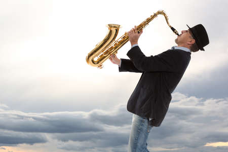 tenor: Saxophonist. Man playing on saxophone against the background of sky Stock Photo