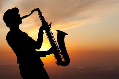 saxof�n: Saxofonista. Mujer que toca el saxof�n en el contexto de la puesta del sol Foto de archivo