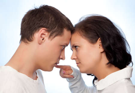 Young couple quarreling against a blue background photo