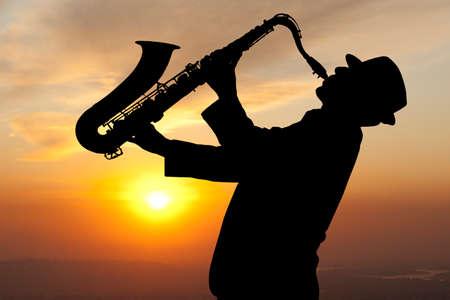 サックス奏者。夕日を背景にサクソフォーンで遊んで男