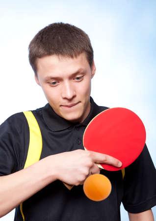pingpong: Hombre joven que juega a ping pong contra un fondo azul Foto de archivo
