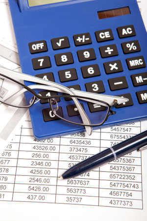 Glasses and calculator on paper table with finance report  photo