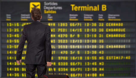 working late: Businessman with a briefcase on a background of departure board at airport