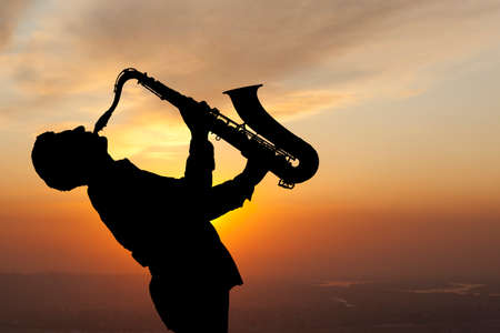 Saxophonist. Man playing on saxophone against the background of sunset photo