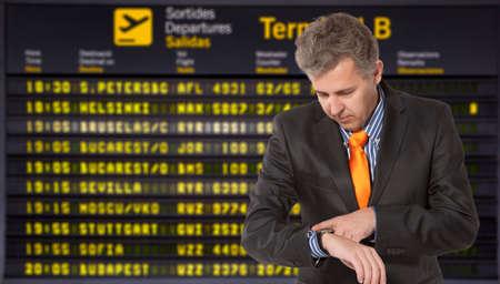Flight delay. Businessman looking at his watch