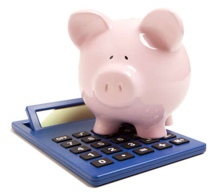 Pink piggy bank and calculator isolated on white background  photo