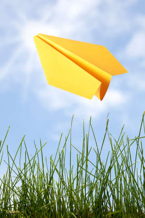 Yellow paper plane in the sky  photo