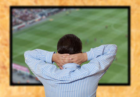 Man watching football game via tv at home  photo