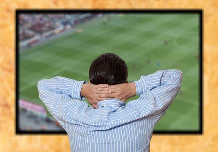 Man watching football game via tv at home  photo