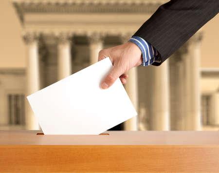 democracia: Mano poniendo una papeleta de votación en una ranura de la caja Foto de archivo