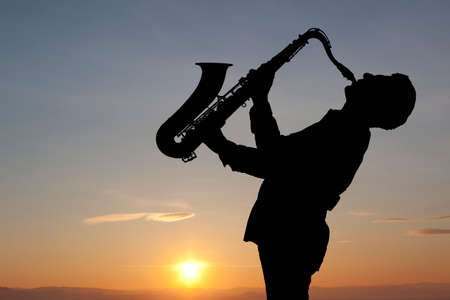 Man playing on saxophone against the background of sunset Stock Photo