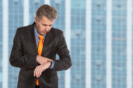 punctual: Adult businessman looking at his wristwatch with cityscape in the background