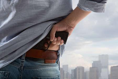 空の背景に対して男を保持している銃