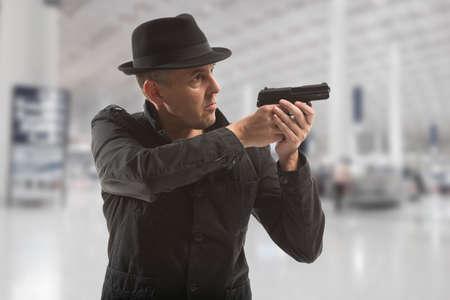 james bond: secret service man with gun on grey background Stock Photo