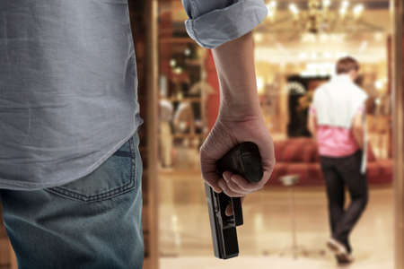 Man Holding Gun against an hotel background