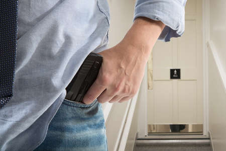water closet: Bodyguard with gun protects client against an s water closet door background