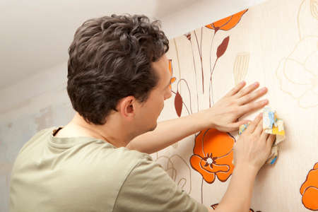 Decorator hanging wallpaper.  Repair and home concept