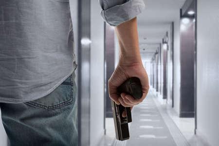 Man met het pistool tegen een corridor achtergrond Stockfoto