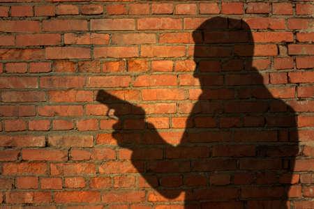 silueta humana: Silueta humana con arma de fuego en la sombra en el fondo de la pared de ladrillo