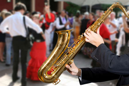 Saxophonist. Men playing on saxophone against the background of dance people photo