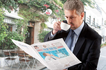 Businessman reading a newspaper while drinking coffee photo