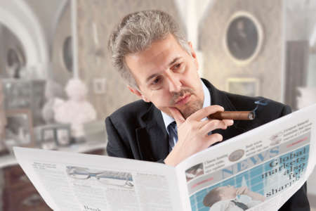 Businessman reading a newspaper while smoking cigars photo