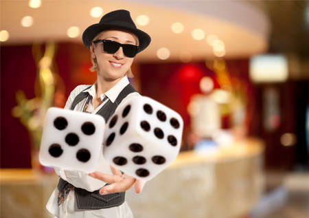 Blonde Woman in a hat playing dice  Stock Photo