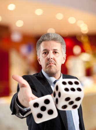 Man in a suit playing dice