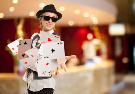 Bluff, happy blonde woman in cap playing with poker cards photo