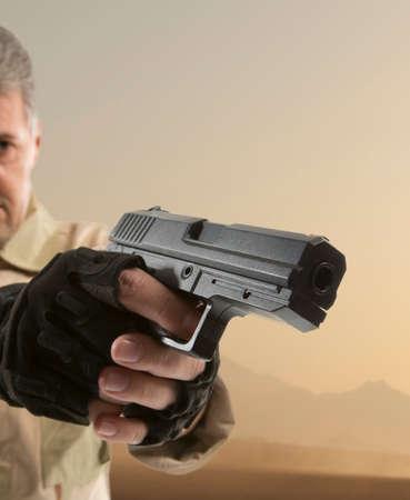 man holding gun: Man Stock Photo