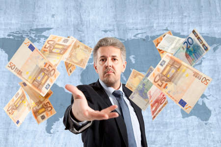 Handsome adult businessman throwing euro photo