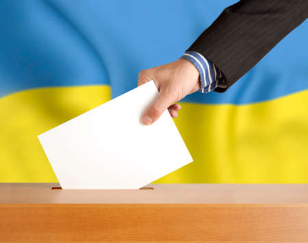 plebiscite: Male hand with ballot and box on Flag of Ukraine