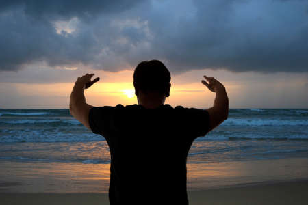 Man with his hands up on the dawn on the beach photo