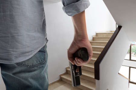 Man holding gun against an stairs background Stock Photo