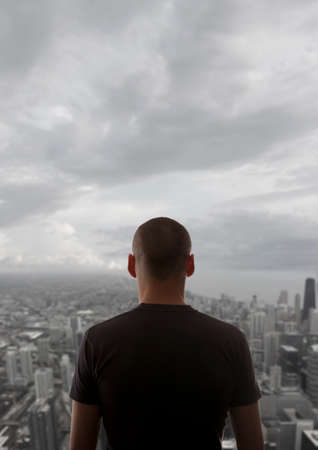 exult: Men standing on the rooftop of a skyscraper over a cityscape Stock Photo