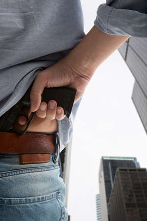 man holding gun: Man holding gun against an skyscraper background  Stock Photo