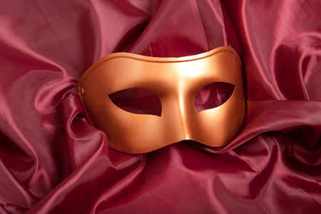 contrasts: Golden carnival mask on red satin background  Stock Photo