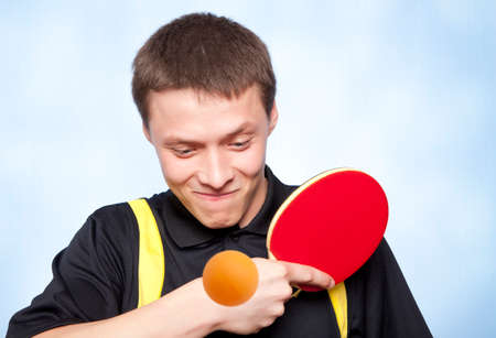 Young man playing ping pong against a blue background  photo