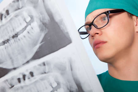 Young doctor dentist with jaw xray on blue background photo