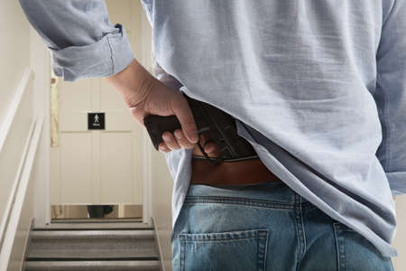 water closet: Bodyguard with gun protects client against water closet door background Stock Photo